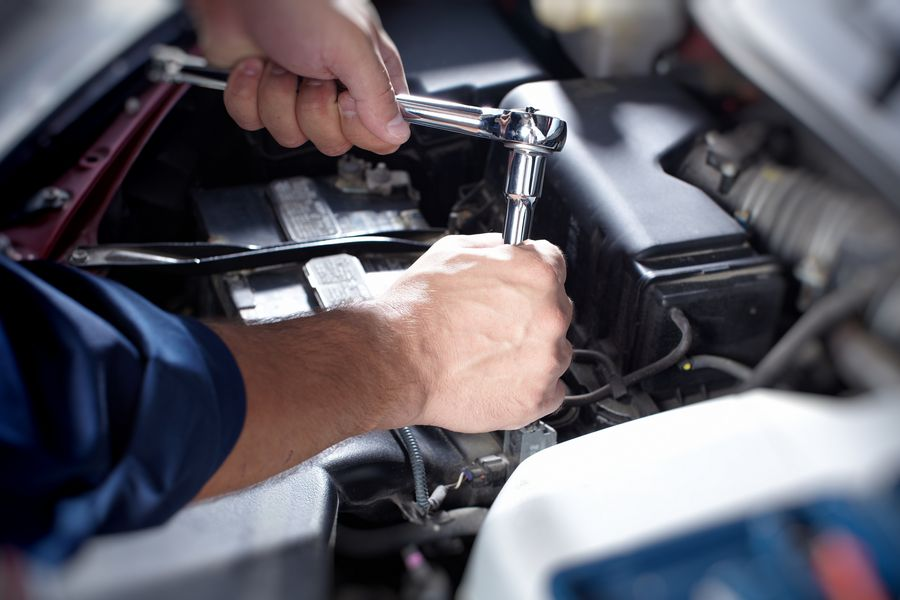 Mechanic working in auto repair garage, car maintenance