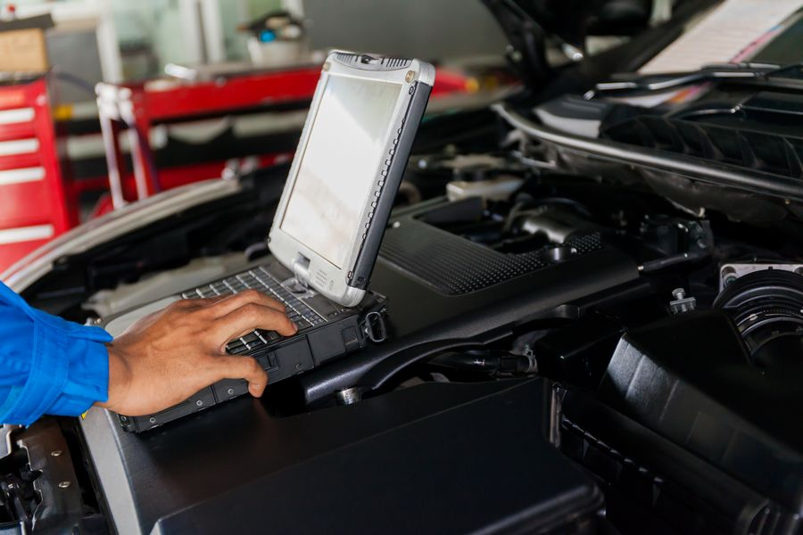 Mechanic using diagnostic tool in car
